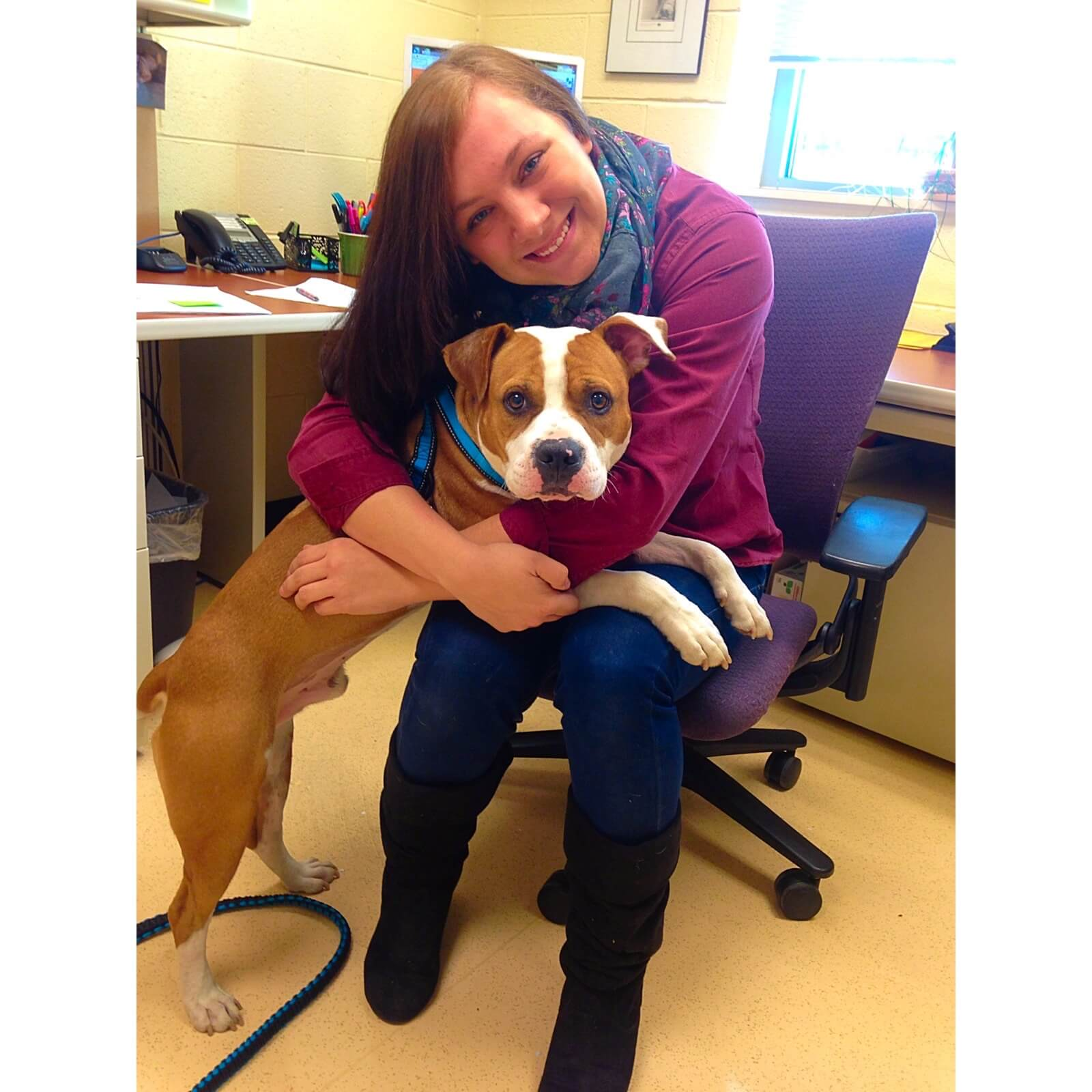 "A staff member says ""goodbye"" to her foster dog who was adopted after going through surgery for a leg wound."